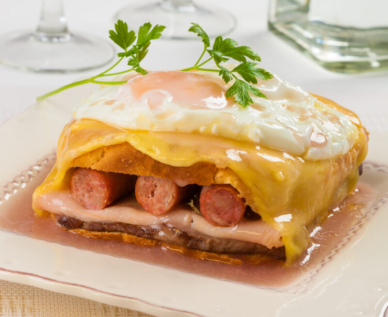 A large sandwich with three sausages, ham and an egg on top.