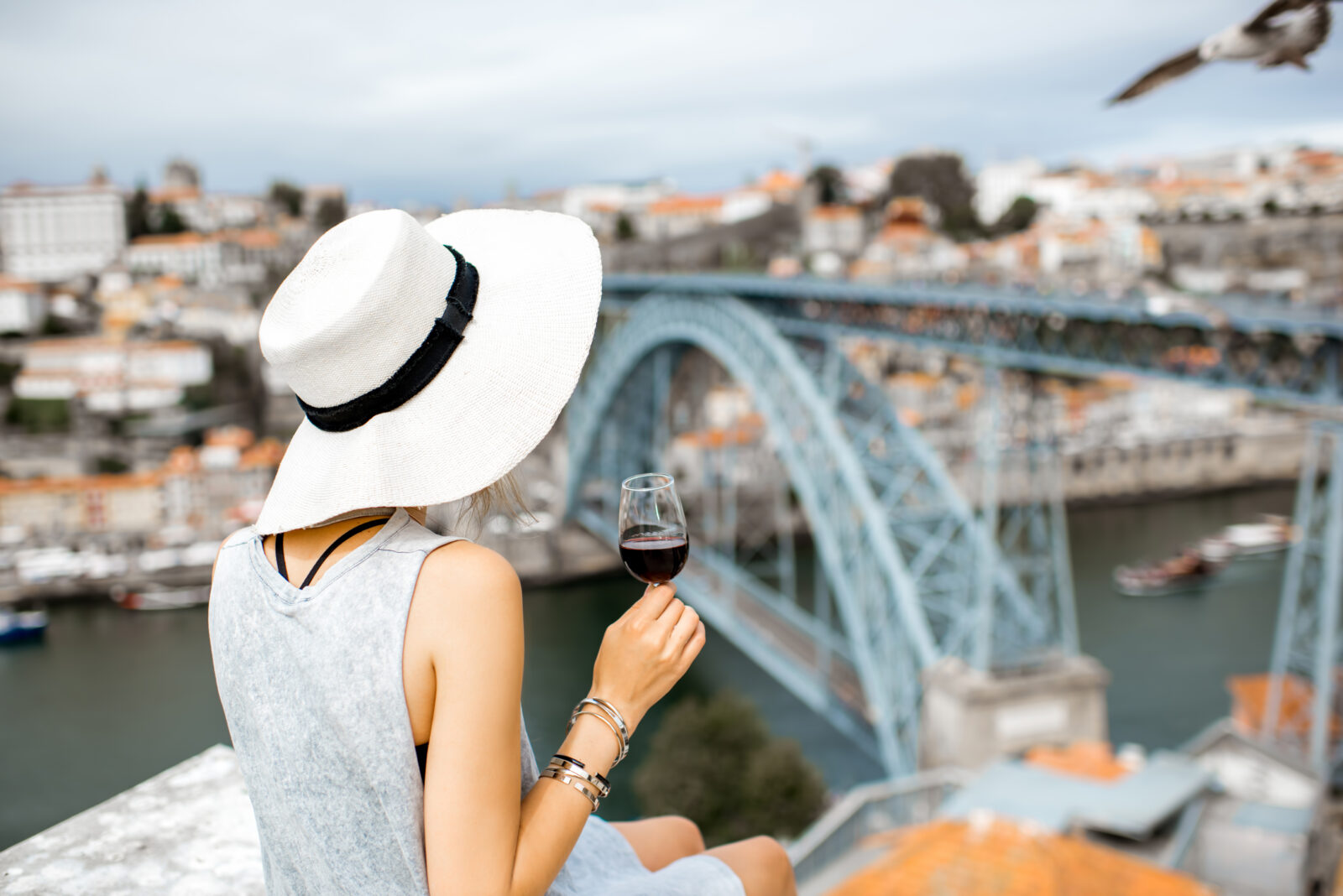 Woman in hat drinks wine by a bridge
